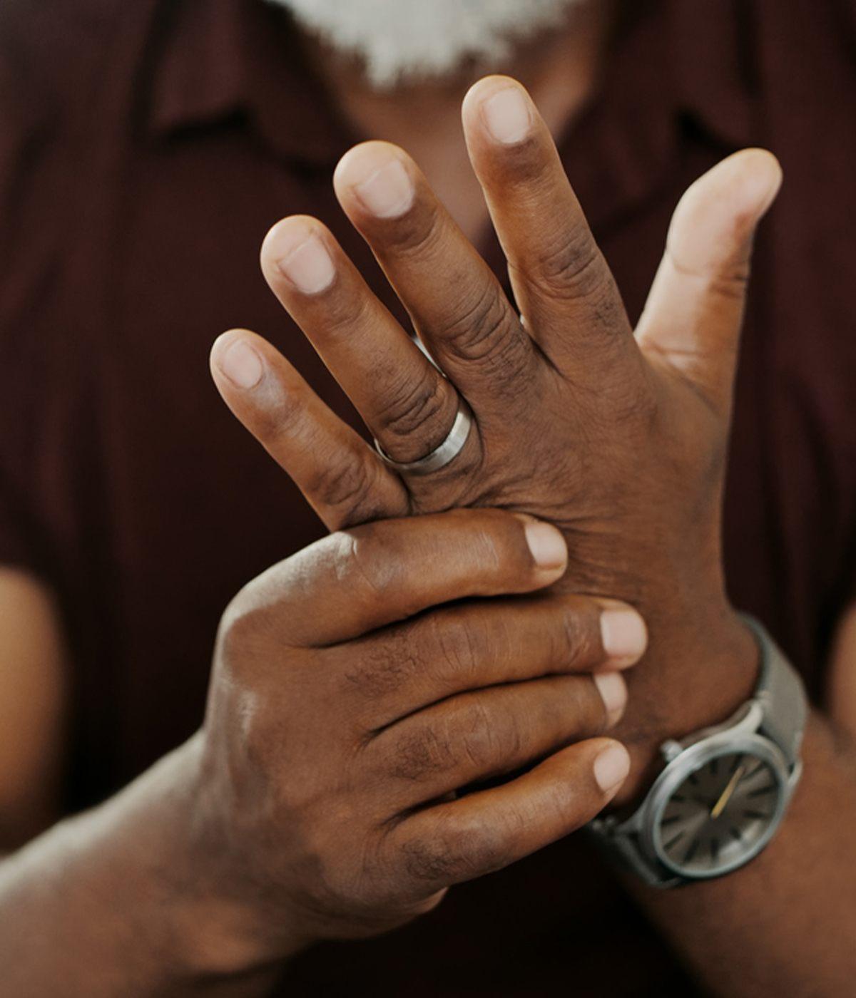 Man holding hand because of pain caused by Rheumatoid Arthritis